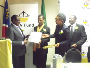 On the left, Hon. Joel Kaapanda, Minister of Information and Communication Technology cutting the  ribbon while Dr Zandile Erkana MVA Fund Board of Directors holds the brochure, and flanked by Rosalia Martins-Haufiku (right), MVA Fund Chief Executive Officer.