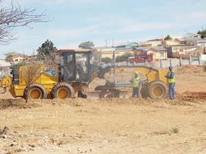 Grader grading graves: The City of Windhoek workers busy on the extension of the Oponganda Cemetery, which they anticipate to be completed by December 2014 to make more burial space available. (Photograph by Mandisa Rasmeni)