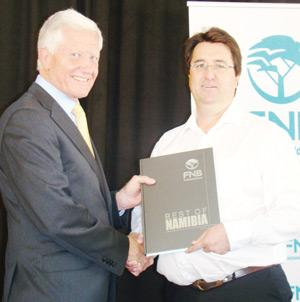 Brand Pretorius, retired Chief Executive Officer of McCarthy Motor Holdings on the left receives a gift from Christo Viljoen Head: FNB Agri Division