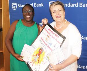 Surihe Gaomas-Guchu, Public Relations and Communication Manager, Standard Bank Namibia presenting Reneitte Koegelenberg, Chief Executive Officer of the Cancer Association with a N$120,000 donation earlier this week.