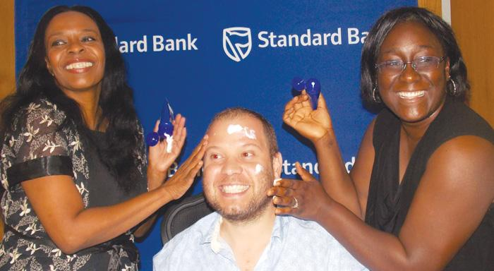 Advocate Sigrid Tjijorokisa (left ) and Surihe Gamas-Guchu (right) demonstrating that sun screen is important to prevent skin cancer on Rolf Hansen,CEO of the Cancer. Association. (Photograph by Mandisa Rasmeni).