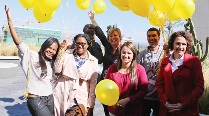 Tracy Eagles (centre back), the Chief Marketing Officer of FNB and Madri Frewer (front right), the Marketing Manager of FNB, introducing the bank's new web-based happiness tool together with their staff. The so-called happiness store enables the transfer of gifts between friends by paying for the gift at participating stores.