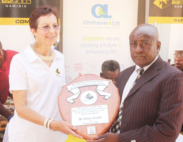 Mr Simon Tsuseb (Director of Education, Arts & Culture for the Otjozondjupa Region) receives a plaque commemorating the classroom handover from Auriol Ashby (Acting CSR Manager, B2Gold Namibia).