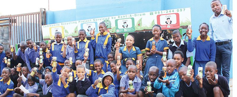 NBL Brand Manager: VIGO, Ndapandula Hatuikulipi (left) and Namibia Primary School teacher, Dumie Litwayi  are joined by some of the learners at one of the new VIGO-branded recycling stands  constructed for the annual Recycle Namibia Forum (RNF) Schools Recycling Competition.